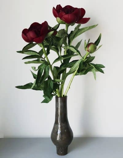 Red peonies in handturned ceramic vase