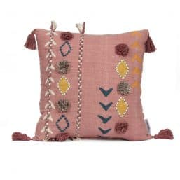 pink cushion with pom poms