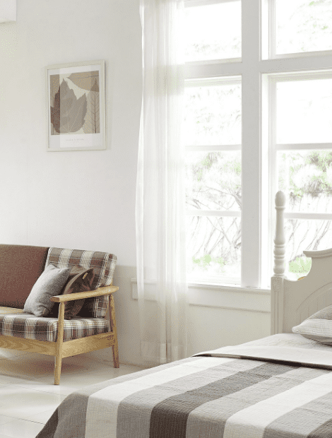 White curtains letting in natural light in a bedroom